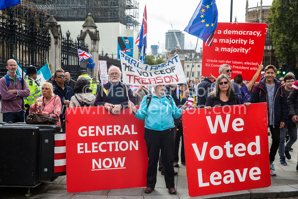 """London, UK. 25 September, 2019. Pro- and anti-Brexit activists protest outside the Houses of Parliament on the day after the Supreme Court ruled that the Prime Minister's decision to suspend parliament was """"unlawful, void and of no effect""""."""