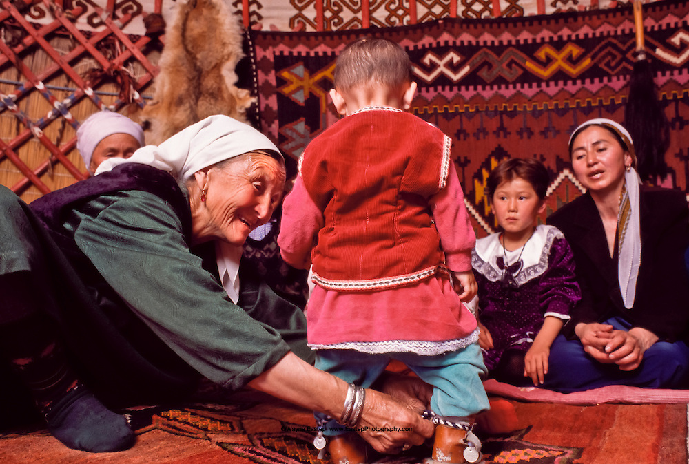 Kazakh grandmother ties a cord around the ankles of the toddler marking the first step  Shieli, Kazakhstan