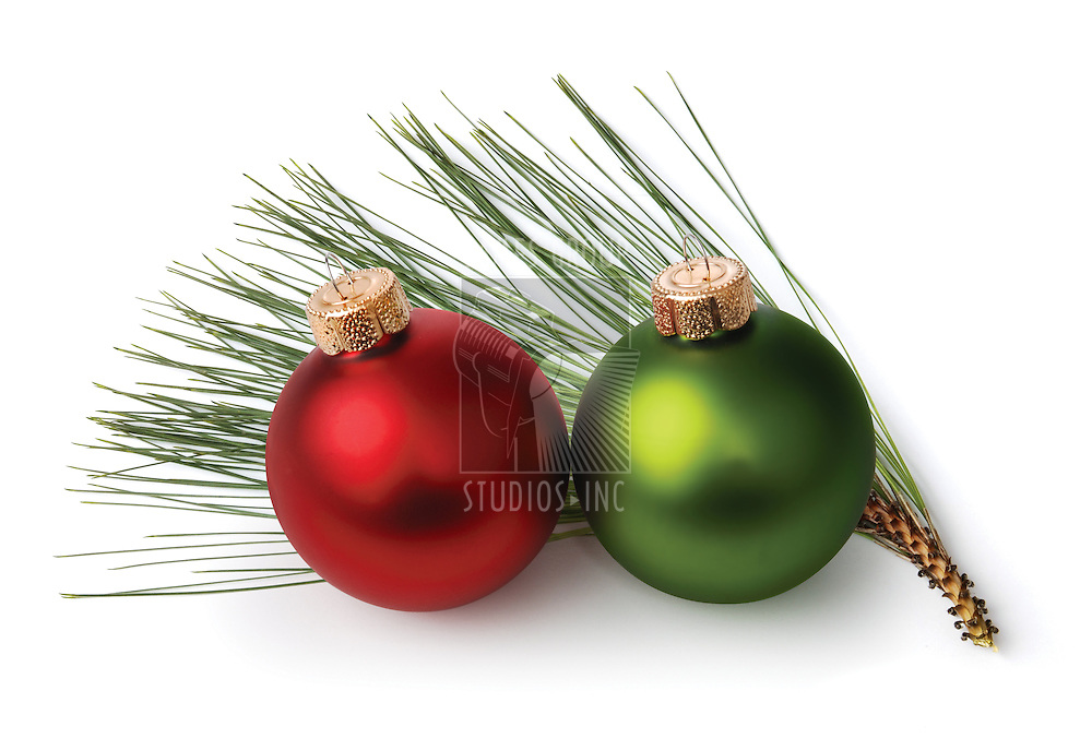 red and green Christmas ornaments in front of a sprig of pine needles