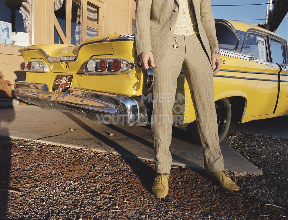 Waist down view of man standing in front of long yellow car.