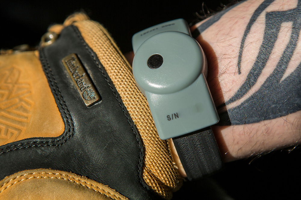 A Prison tag on a released prisoner sometimes known as a Rolex. Electronic tags can be fitted to the wrist or ankle, they allow a constant watch to be kept, making sure that former inmates do not even step outside their front door during curfew hours. If the prisoner breaks their curfew, the electronic tag will alert the contractors and the prisoner may be recalled to prison. HMP/YOI Portland, Dorset, United Kingdom.