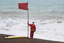© Licensed to London News Pictures. 31/05/2015. Brighton, UK. A lifeguard watches the sea in case of an emergency. The red flag was raised on the beach due to strong wind and high waves, today May 31st 2015. Photo credit : Hugo Michiels/LNP