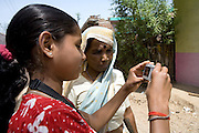 Pooja, 14, a student from the village of Pathpuri, Hoshangabad, Madhya Pradesh, India, taking part to the children's journal, a project launched by Dalit Sangh, an NGO which has been working for the uplift of scheduled castes for the past 22 years, is showing a picture shot with a digital camera provided by the project to child reporters to a woman living in the village. Dalit Sangh is working in collaboration with Unicef India to promote education and awareness within backward communities.