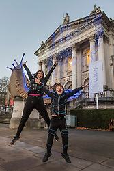"© Licensed to London News Pictures. 30/11/2018. LONDON, UK. Turner Prize nominated artist Monster Chetwynd and son Dragon pose in front of her new Tate Britain Winter Commission.  The artist, formerly known as ""Marvin Gaye"" and ""Spartacus"", has transformed Tate Britain's iconic Neo-Classical façade to mark the winter season with a new piece inspired by the winter solstice, involving a dazzling light display and elements of sculpture.  Winter Commission 2018: Monster Chetwynd will be switched on daily from 1st December 2018 - 28 February 2019.  Photo credit: Stephen Chung/LNP"