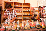 Colour Sand artist fills bottles with colourful desert sand for sale to tourists Photographed in Jerash, Jordan