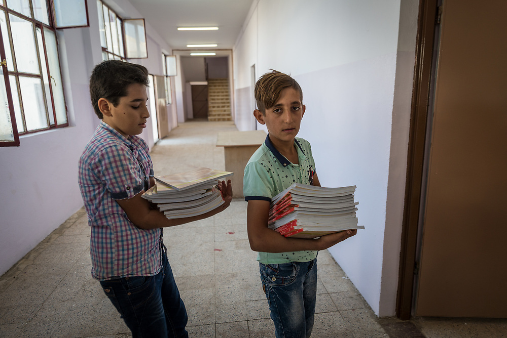 11 October 2017 &ndash; Ninewa Plains &ndash; Iraq &ndash; Students at Al-Taghllubia School for Boys in the Ninewa Plains carry books into a classroom on the first day the school reopened its doors after being closed for 3 years. <br /> <br /> &ldquo;There was no one here for 3 years after ISIL came,&rdquo; said Principal Jubrail Ibrahim. &ldquo;The students went to Erbil, Duhok, Baghdad, Kirkuk. Today is the first day the pupils came back to their school. It&rsquo;s made us all very happy.&rdquo; UNDP&rsquo;s Funding Facility for Stabilization is helping rehabilitate the school. <br /> <br /> &copy; UNDP Iraq / Claire Thomas