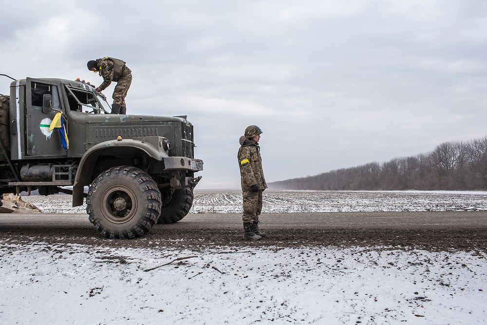 Ukrainian soldiers from a unit based in Zaporizhia repair the bullet-shattered windshield of a truck after taking fire during their withdrawal from Debaltseve the previous day on February 19, 2015 in Artemivsk, Ukraine. Ukrainian forces started withdrawing from the strategic and hard-fought town of Debaltseve yesterday being effectively surrounded by pro-Russian rebels.