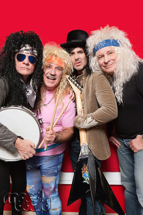 Four male friends wearing hippie clothes and posing