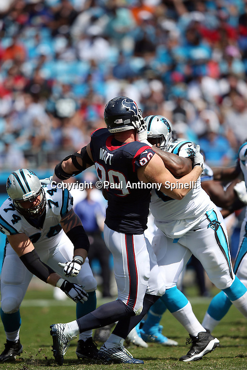 Houston Texans defensive end J.J. Watt (99) gets  double team blocked by Carolina Panthers tackle Michael Oher (73) and Carolina Panthers tackle Mike Remmers (74) during the 2015 NFL week 2 regular season football game against the Carolina Panthers on Sunday, Sept. 20, 2015 in Charlotte, N.C. The Panthers won the game 24-17. (©Paul Anthony Spinelli)