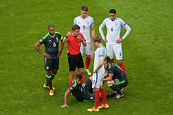 LENS, FRANCE - Thursday, June 16, 2016: Referee Felix Brych signals for medical attention as Wales' Joe Ledley looks towards the bench as he sits injured on the pitch during the UEFA Euro 2016 Championship Group B match against England at the Stade Bollaert-Delelis. (Pic by Paul Greenwood/Propaganda)