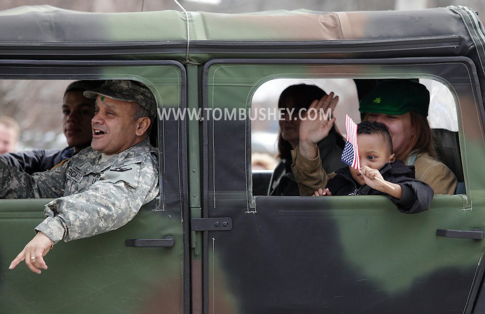 Goshen, New York - People in a military vehicle wave to the crowd while driving in the mid-Hudson St. Patrick's Day parade on March 13, 2011. ©Tom Bushey / The Image Works