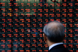 Man looking at prices of stocks on electronic display in Tokyo