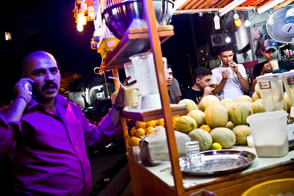 Men gather around a juice stand in Karadah district, Baghdad in Iraq.