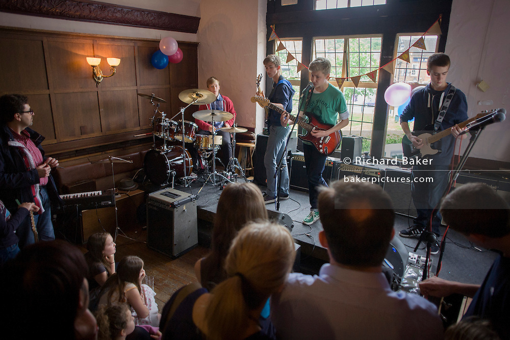 A teenage 4-piece band of drums, bass and two lead guitars perform in front of parents in an upstairs pub room in south London. 15 year-old lads play their own songs and covers by other musical artists.