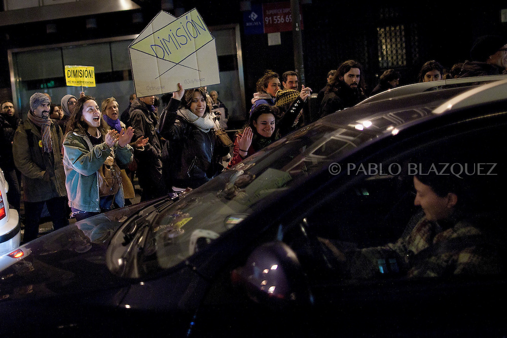 Protesters walk in the streets while a woman inside a car plays the klaxon in support to them during a demonstration against political corruption and claiming Mariano Rajoy to resign in Madrid on February 1, 2013. The Spanish Newspaper 'El Pais' published secret papers of income implicating Spanish Prime Minister and other members of the PP (Popular Party). Rajoy's government has denied these secret payments.