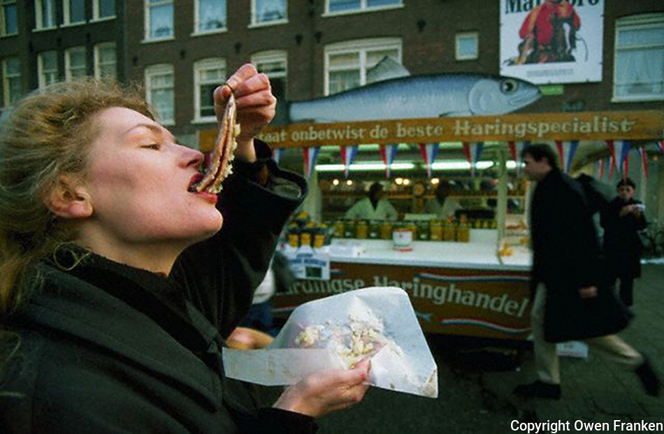 January 1991, Amsterdam, Netherlands --- A woman eats Dutch herring in Amsterdam, Netherlands --- Image by © Owen Franken/CORBIS