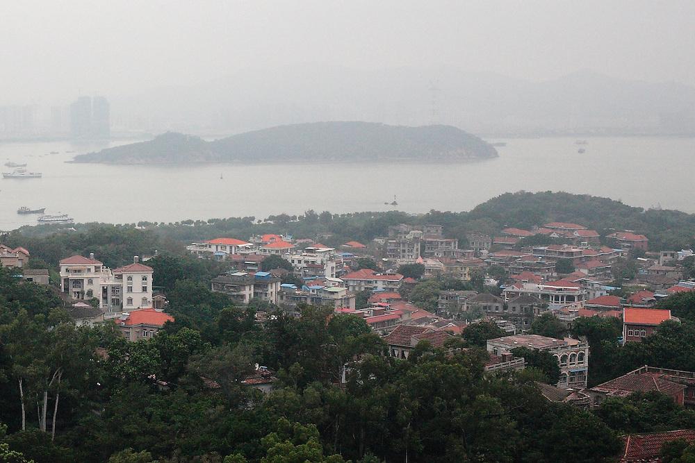 L'architecture des maisons coloniales se détache dans la brume du matin sur l'ile Gulangyu, isolée du monde contemporain de Xiamen dont les tours apparaissent à l'arrière plan derrière le brouillard.