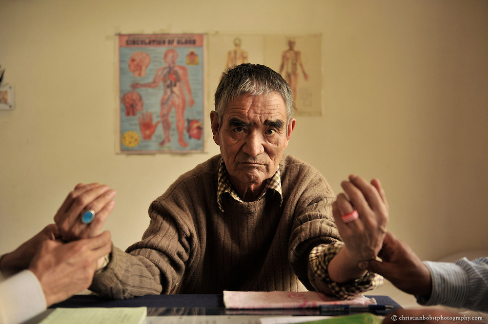 An old man is examined by a Tibetan doctor and his assistant at a tibetan hospital in Manali, India, 2009