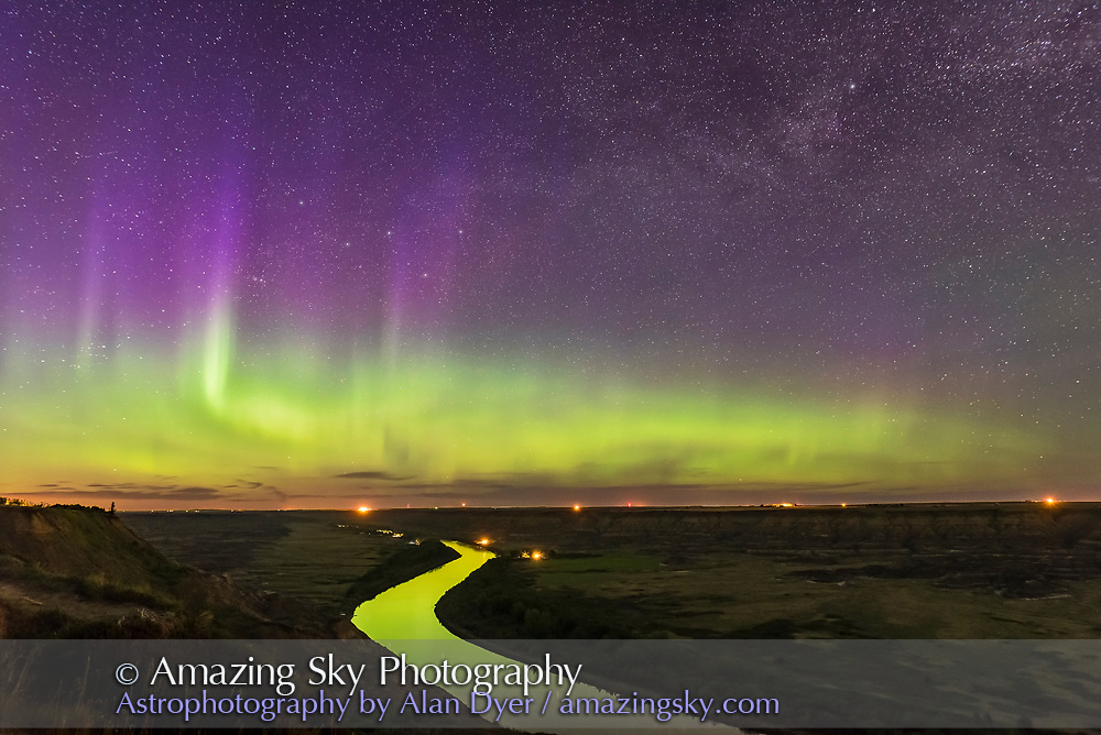 The Northern Lights dance over the sweeping Red Deer River and Badlands of southern Alberta, from Orkney Viewpoint looking north over the valley. The Bleriot Ferry crossing is in the distance at the lights. Cassiopeia is embedded in the purple curtains. The river reflects the aurora light. <br /> <br /> This is a stack of 4 x 15-second exposures for the ground to smooth noise, and one 15-second exposure for the sky, all with the 20mm Sigma lens at f/2.8 and Nikon D750 at ISO 3200. They were part of a 250-frame time-lapse.