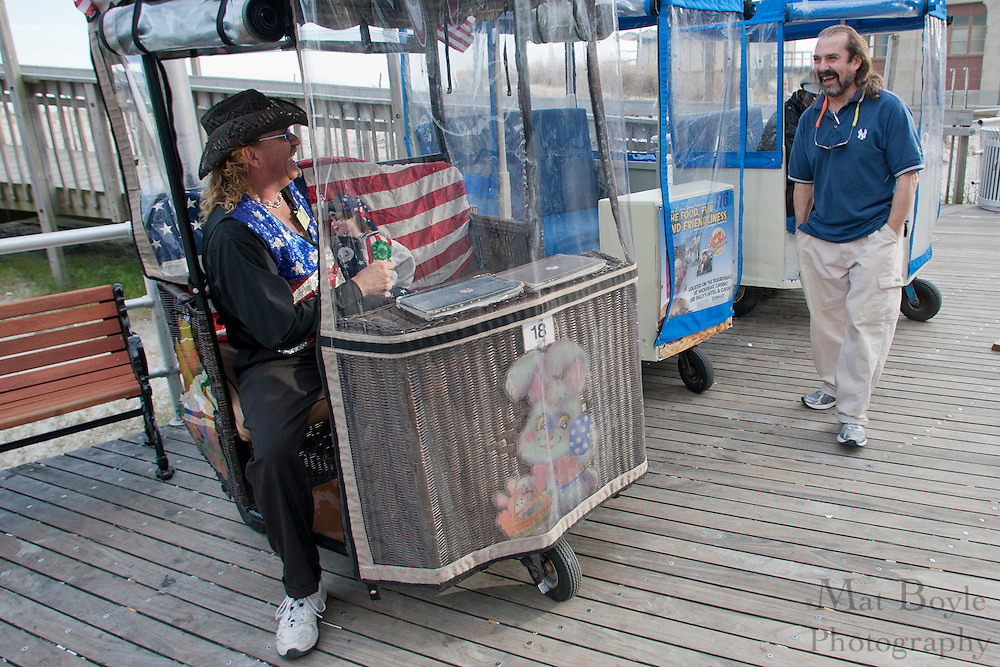 "Atlantic City NJ rolling chair operator ""The Caiptain"", Joseph Rechten, talks with a fellow rolling chair operator while ating for customers on April, 21, 2011."
