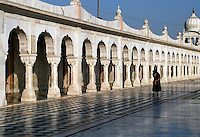 A man walking along the pool in the Bangla Sahib Gurdwara, in Delhi, India