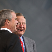 Pres. Bush, alongside former President George H W Bush and former First Lady Barbara Bush, christen CVN-77 George H W Bush aircraft carrier Saturday, October 7, 2006, in Newport News, Virginia.  CVN-77 is the 10th and final of the Nimitz-class aircraft carriers.  It is set to replace the USS Kitty Hawk in 2008...Photo by Khue Bui