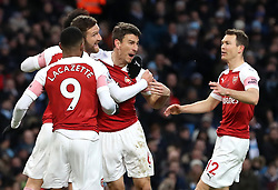 Arsenal's Laurent Koscielny (second right) celebrates his side's first goal of the game with teammates during the Premier League match at the Etihad Stadium, Manchester.