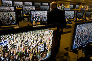 Shopper watches Barack Obama Democrat supporters stage rally seen on BBC News TV screens in John Lewis department store