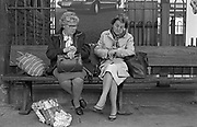 After a shopping trip, two ladies check the time on their watches before catching their train from Newport station, 1985