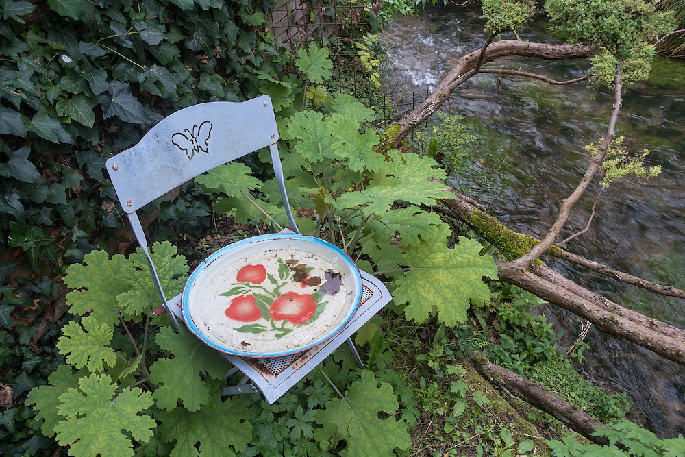 A pale blue metal chair with a butterfly motif on its back and a rusty plate decorated in a red floral pattern resting on the seat is surrounded by leafy green vines and trees. A brook meanders to the right.