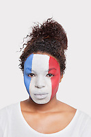 Portrait of young African American woman with French flag painted on face against white background