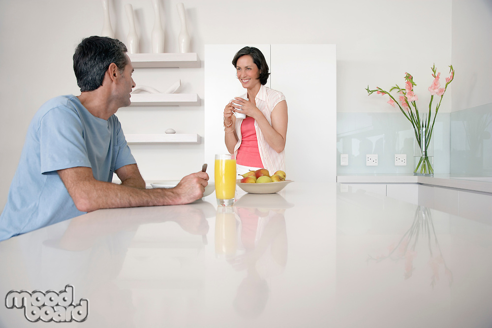 Couple having breakfast at kitchen bench