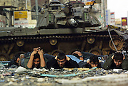 Palestinian male detaniees are forced by the Israeli army to lay on the ground before and Israeli tank  in the center of Ramallah March 30,2002. (Photo by Heidi Levine/Sipa Press).