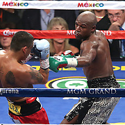 LAS VEGAS, NV - SEPTEMBER 13: Floyd Mayweather Jr. (R) steps into Marcos Maidana during their WBC/WBA welterweight title fight at the MGM Grand Garden Arena on September 13, 2014 in Las Vegas, Nevada. (Photo by Alex Menendez/Getty Images) *** Local Caption *** Floyd Mayweather Jr; Marcos Maidana