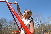 Sarah Whisman, member of the Club Field Hockey Team, paints a swingset at Highland Park for Athens Beautification Day.