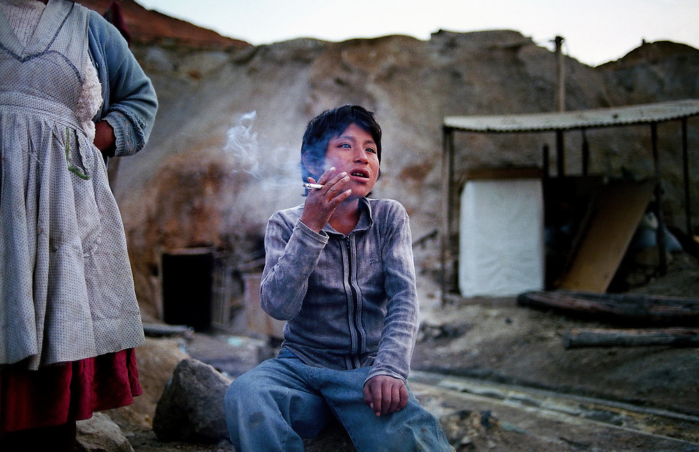 Santiago Solis, 11 old, is smoking a cigarette in front of his house in Cerro Rico silver exploitation. His father died in a mine accident and he lives together with his mother,Angelica, 37, scouring for pieces of silver left in the discarded rocks.