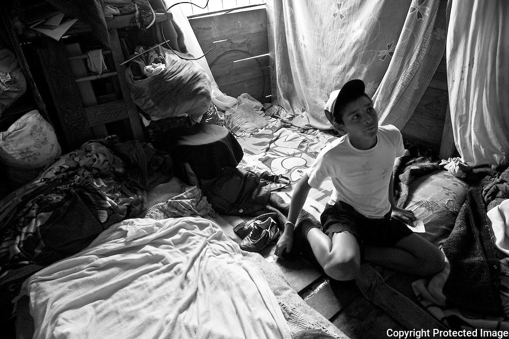 Isreal sits on his matress in the room he share with hhis Mother, Father and little brother. The beds are wet from the rain because there is no metal sidding on the outside of their wooden shack. Without this protection water always seeps in leaving the bedding damp.