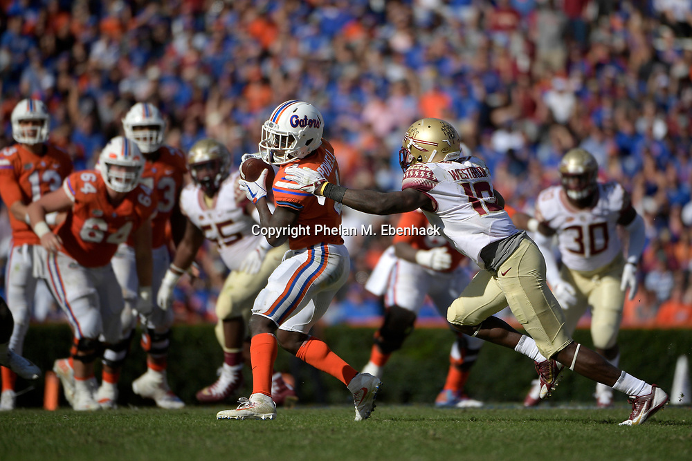 Florida wide receiver Brandon Powell (4) catches a pass in front of Florida State defensive back A.J. Westbrook (19) during the second half of an NCAA college football game Saturday, Nov. 25, 2017, in Gainesville, Fla. FSU won 38-22. (Photo by Phelan M. Ebenhack)