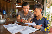 ICS volunteer Ratha Chea sits in a cafe helping a school child with his homework in the village of Banteay Char, near Battambang, Cambodia.