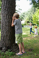 Boy (5-6) standing by tree with eyes covered children running in background