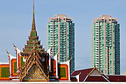 09 JULY 2011 - BANGKOK, THAILAND: A condominium development on the Chao Phraya River sits behind a large Buddhist temple in Bangkok, Thailand.   PHOTO BY JACK KURTZ