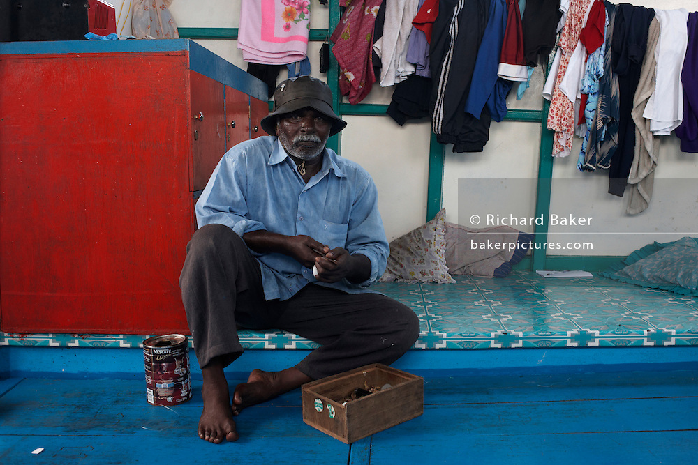 A Maldivian crewman cuts betel nut before a day's yellow fin tuna fishing on traditional dhoni fishing boat on the Indian Ocean