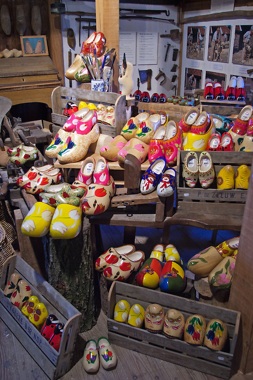 """A variety of decorated wooden shoes on display at the shoemaker's shop in Zaanse Schans, a popular day trip for Amsterdam visitors.  .From Wikipedia: """" Zaanse Schans is a neighbourhood of Zaandam, near Zaandijk in the municipality of Zaanstad in the Netherlands, in the province of North Holland. It has a collection of well-preserved historic windmills and houses; the ca. 35 houses from all over the Zaanstreek were moved to the museum area in the 1970s. The Zaans Museum, established in 1994, is located in the Zaanse Schans..The Zaanse Schans is one of the popular tourist attractions of the region and an anchor point of ERIH, the European Route of Industrial Heritage. The neighbourhood attracts approximately 900,000 visitors every year..The windmills were built after 1574."""".Also from Wikipedia: """" Along the river Zaan, you can find still dozens of original windmills (mostly entirely made of wood), still technically functioning, some of them over 350 years old. Next to these there are many 19th century stone industrial buildings, nowadays derelict or converted into apartments, but still recognisable as industrial buildings.""""."""