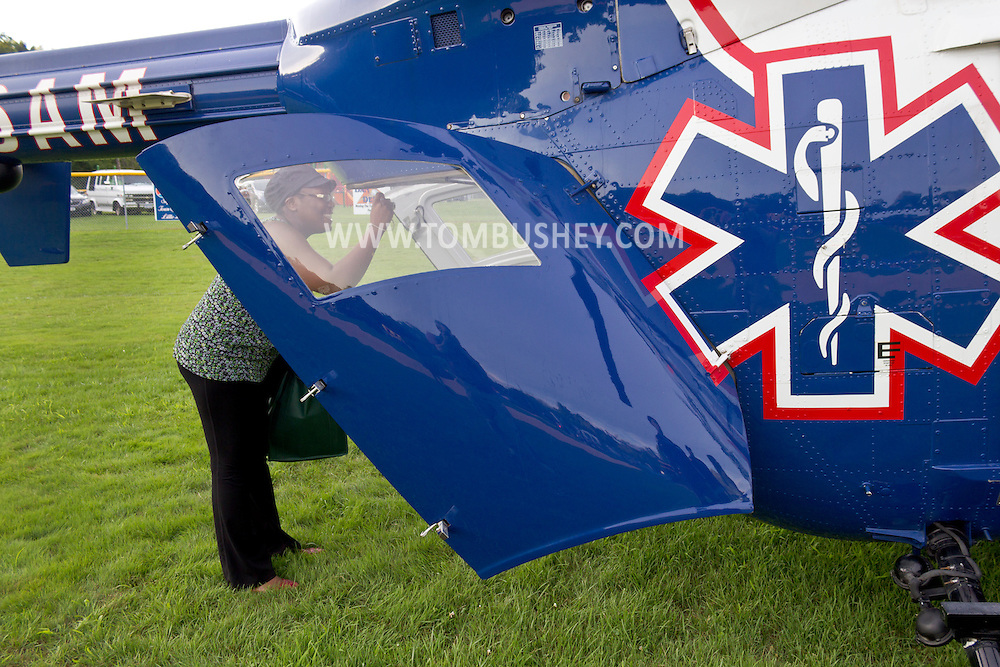 Scotchtown, New York - A woman takes a photograph of the inside of a STAT Flight medical evacuation helicopter that landed on the Little League field during a Night Out Against Crime event on on Aug. 7, 2012. The helicopter is a twin-engine American Eurocopter BK-117.