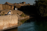 An Afghan man fishes on a tributary of the Helmand River within the walls of a joint U.S.-Afghan base in Sangin District, Helmand Province.