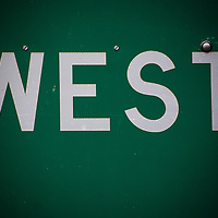 """detailed close up  of interstate road sign with the word """"west.""""  taken on interstate 40 east of albuquerque, new mexico, usa."""