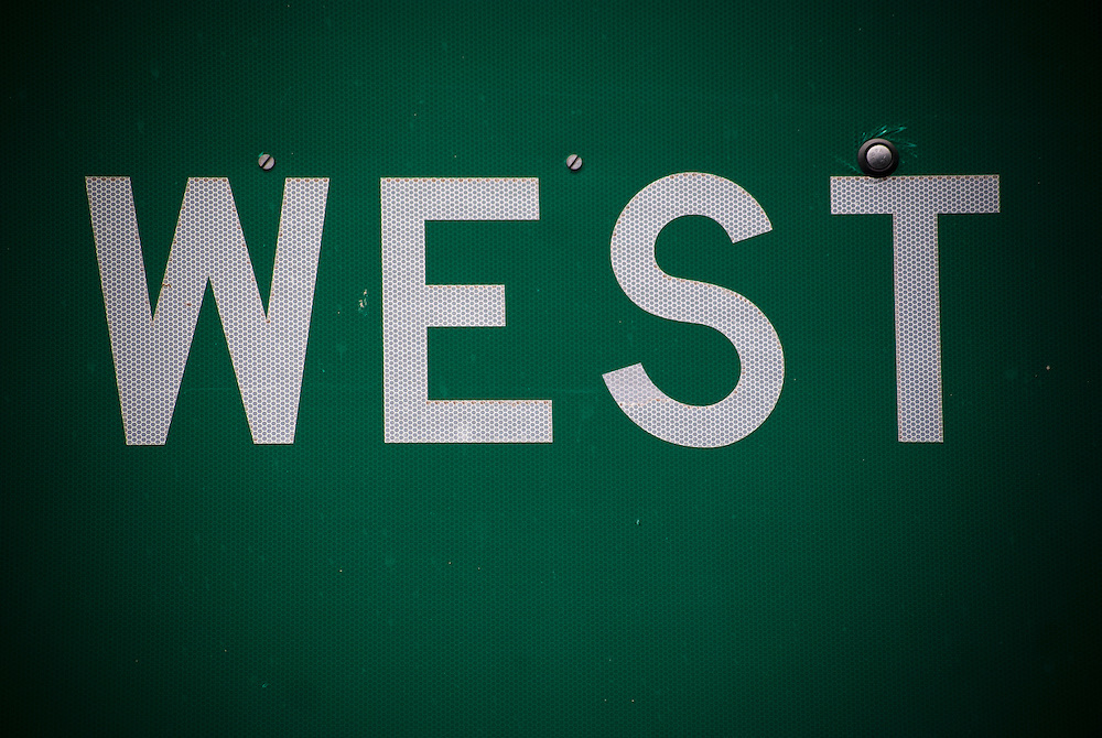 "detailed close up  of interstate road sign with the word ""west.""  taken on interstate 40 east of albuquerque, new mexico, usa."