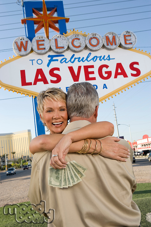 Middle-aged couple embracing in front of Welcome to Las Vegas sign