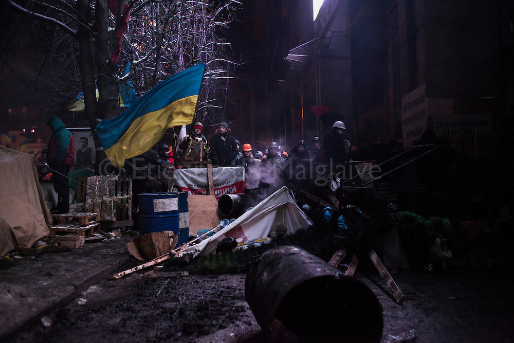 Standing on a barricade at the door of the Trade Unions building on Maidan, protesters face off with the riot police that launched in early morning an intervention to clear partially Maidan Square from anti government protesters. Later, police forces withdraw from the regained grounds. on December 11, 2013 in Kiev, Ukraine. Thousands have been protesting against the Ukrainian government after Ukrainian President Viktor Yanukovych decided to suspend a trade and partnership agreement with the European Union in favor of incentives from Russia.