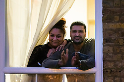 © Licensed to London News Pictures. 02/04/2020. London, UK. People are seen applauding from flat balconies this evening on an estate in Wapping, east London during the 'clap for the NHS' and 'clap for carers' campaigns held in support of the NHS, as the spread of the coronavirus continues. Photo credit: Vickie Flores/LNP